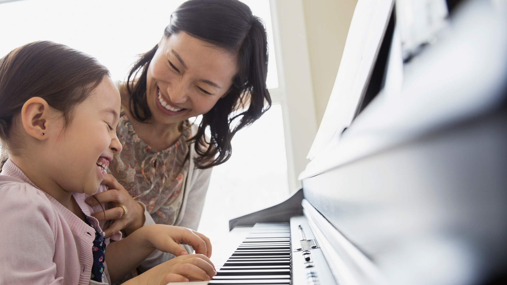 Teacher having fun teaching young girl to play the piano
