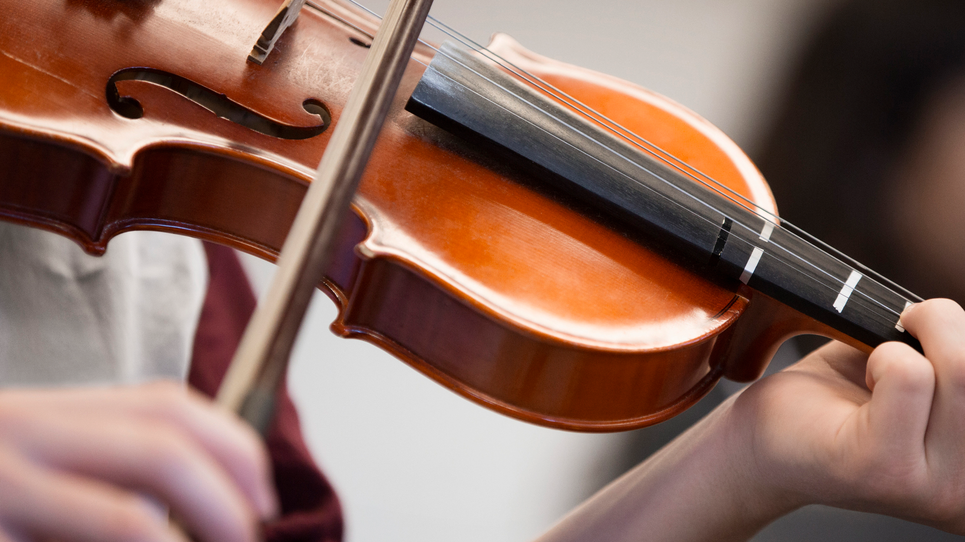 Close up of student of Ping's Music School playing the violin