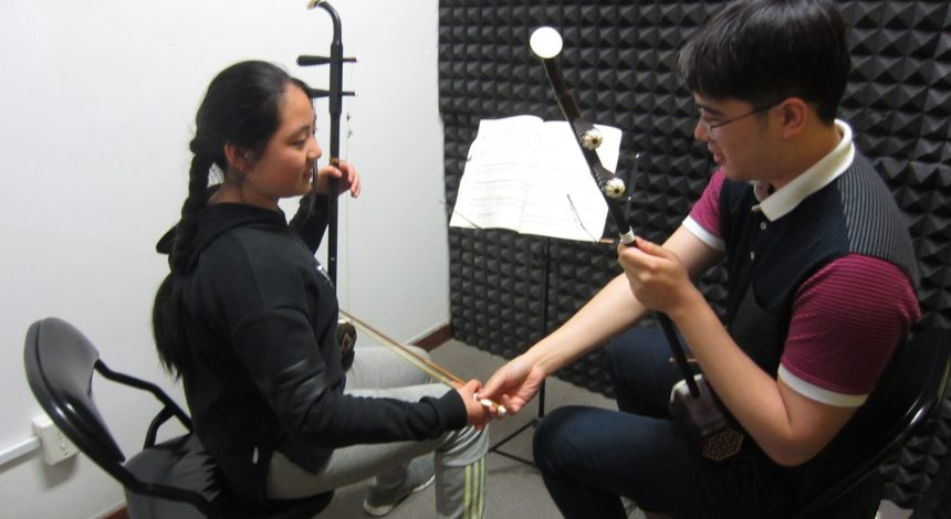 Two students learning the Erhu