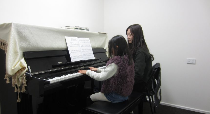 Piano teacher helping a student learn to play the piano