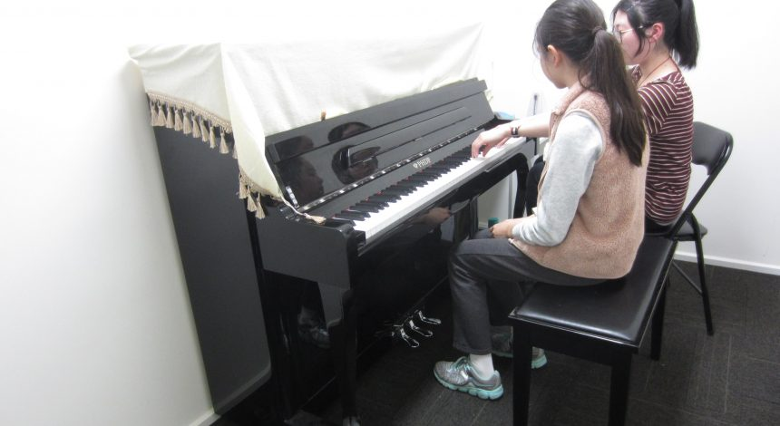 two students learning the piano