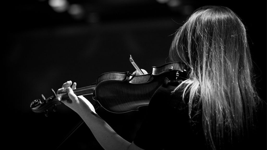 violin student playing infront of a croud