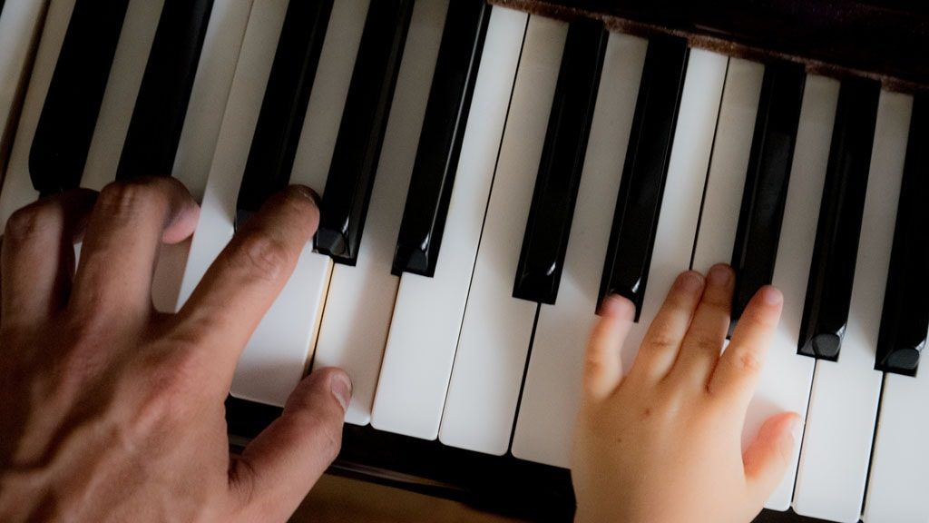 Student and teacher playing the piano