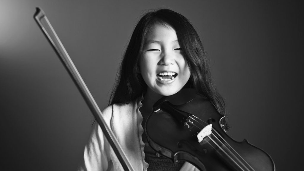 Child student playing Chinese instrument